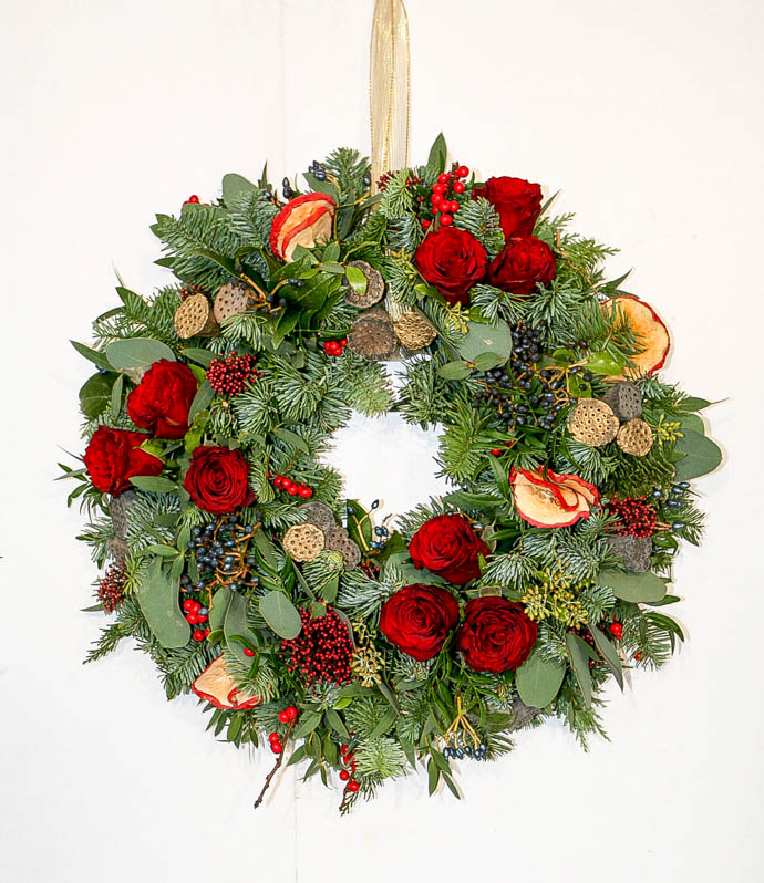 Pine and Fir wreath with fresh red roses, created by Garland, north London Florist