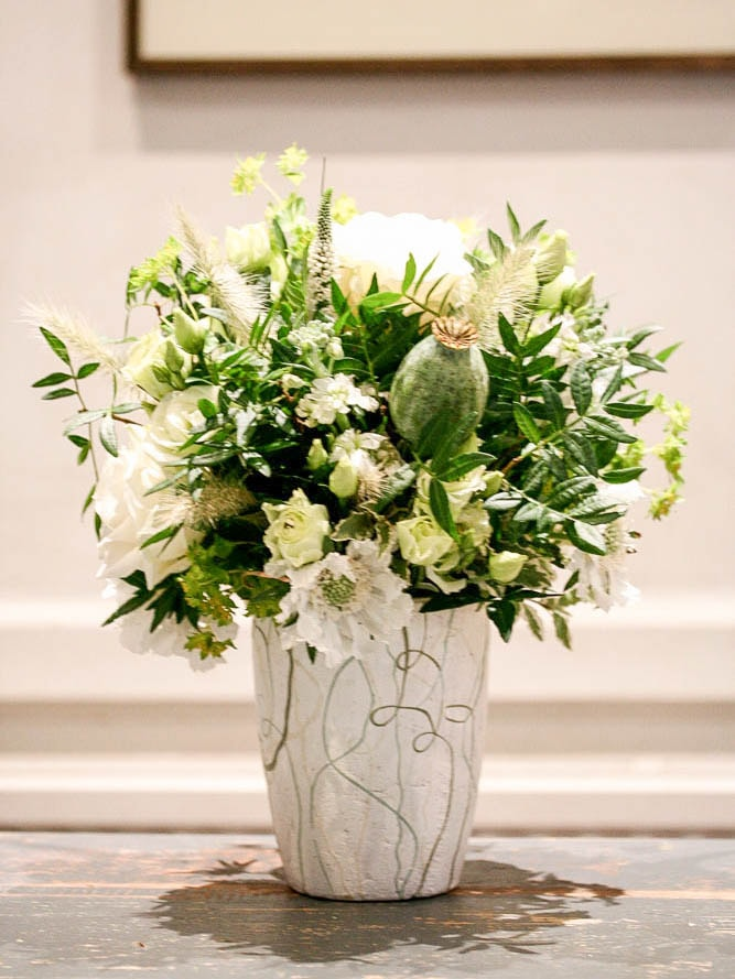 Green and white bouquet in a textured vase, created by north London Florist Garland