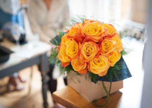 A stunning brides bouquet of light orange roses tinged with a fiery umber, created by London Florist Garland