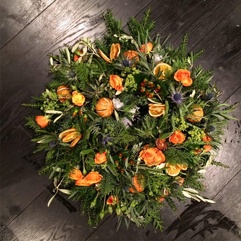 Christmas wreath with orange roses and thistle