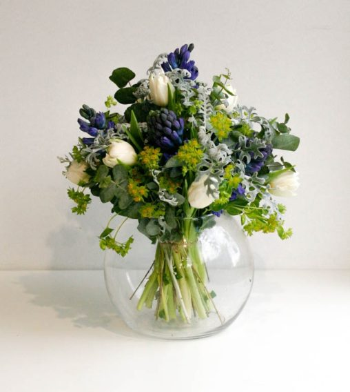 Blue hyacinth and white tulip bouquet in a fish bowl vase, created by London florist Garland
