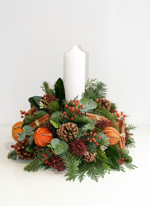 Christmas table decoration with centre candle, oranges, cones and cinnamon, created by London florist Garland