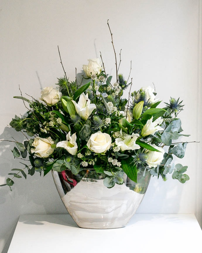 A beautiful Christmas flower arrangement with white roses and lilies, thistle, eucalyptus and silver birch
