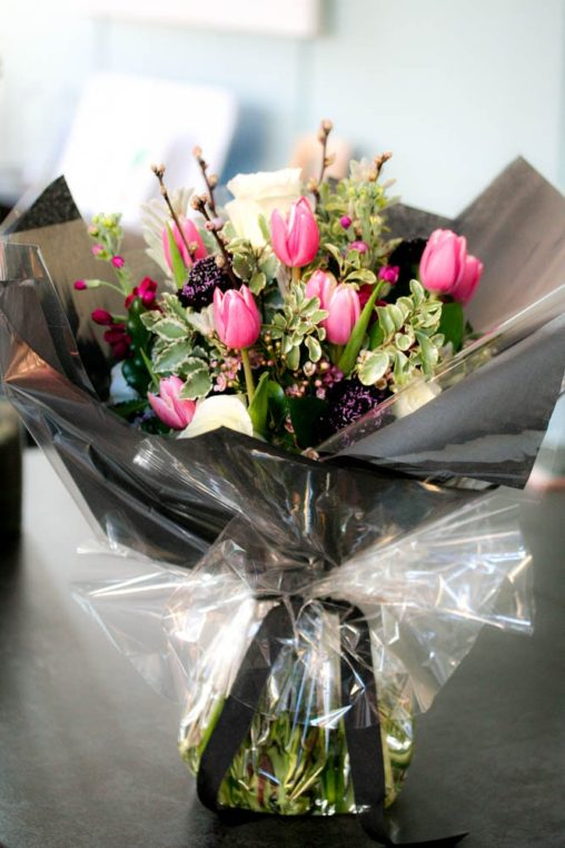 Bouquet of pink tulip, blossom branches and white roses, gift wrapped for birthday delivery, created by Garland, London florist