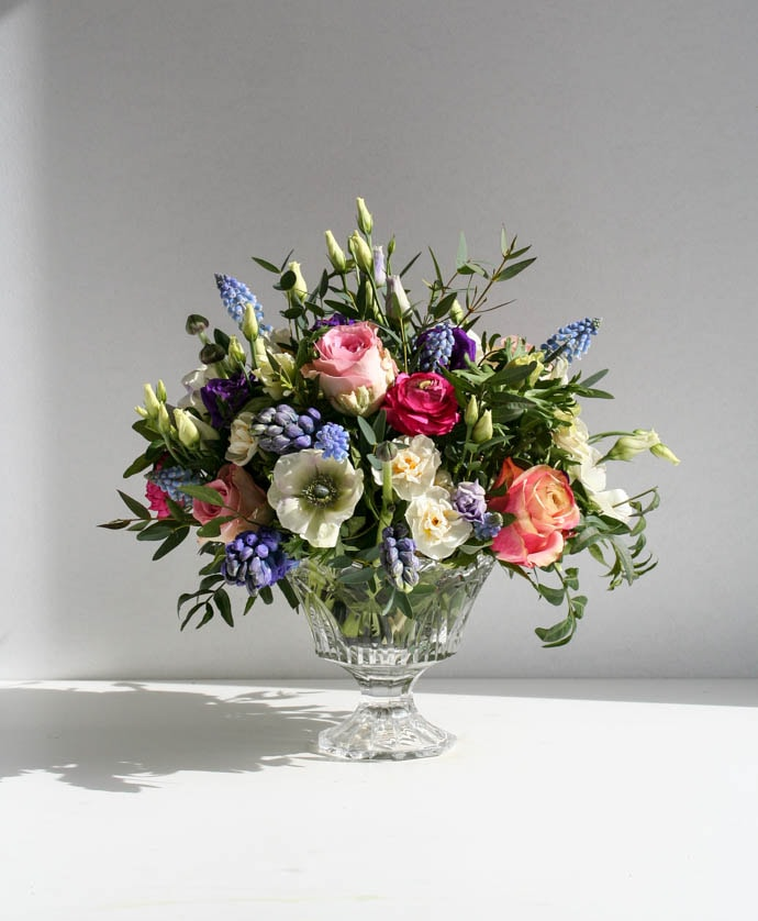 Beautiful cut glass pedestal bowl filled with spring flowers, created by London florist Garland